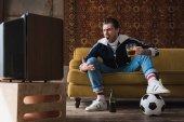 vintage ruhák labda és bögre sört, néz foci a régi TV-vel és kiabálás-kifejező fiatal férfi