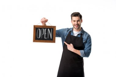 portrait of smiling waiter pointing at open blackboard in hand isolated on white