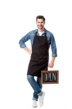 smiling young waiter with open blackboard isolated on white