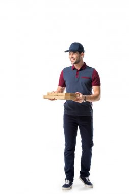 Smiling delivery man with cardboard pizza boxes looking away isolated on white stock vector