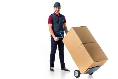 smiling delivery man in uniform pushing hand truck with cardboard boxes isolated on white