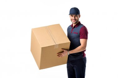 side view of smiling delivery man in cap with cardboard box in hands isolated on white