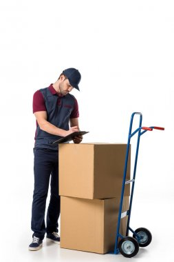 delivery man in uniform checking notes in notepad with cardboard boxes on hand truck near by isolated on white