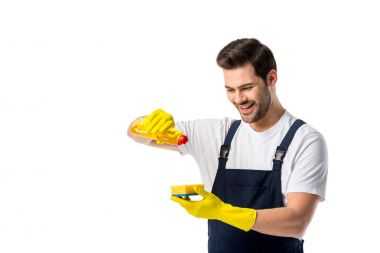 portrait of smiling cleaner in rubber gloves with detergent and sponge isolated on white