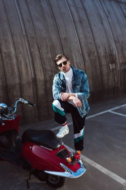 young man in stylish denim jacket with vintage scooter on parking