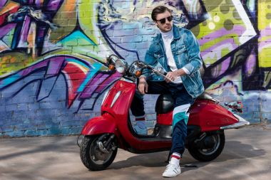stylish young man on vintage red scooter in front of brick wall with graffiti
