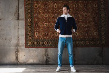 handsome young man in stylish clothes in front of rug hanging on wall
