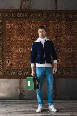 young man with vintage little suitcase in front of rug hanging on wall