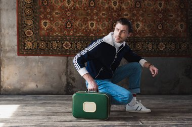 handsome young man with vintage little suitcase sitting squat in front of rug hanging on wall