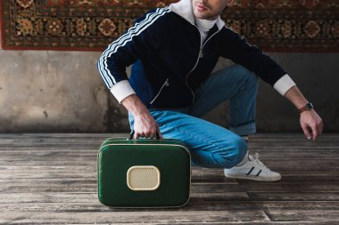cropped shot of man with vintage little suitcase sitting squat in front of rug hanging on wall