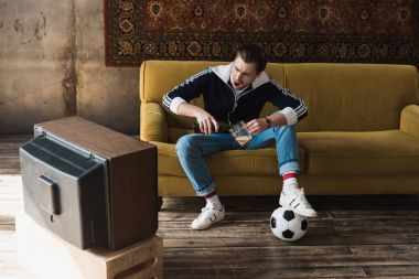 shouting young man in vintage clothes with ball watching soccer on old tv and pouring beer into mug