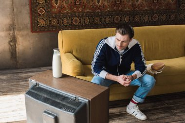 handsome young man in vintage clothes watching tv while sitting on couch