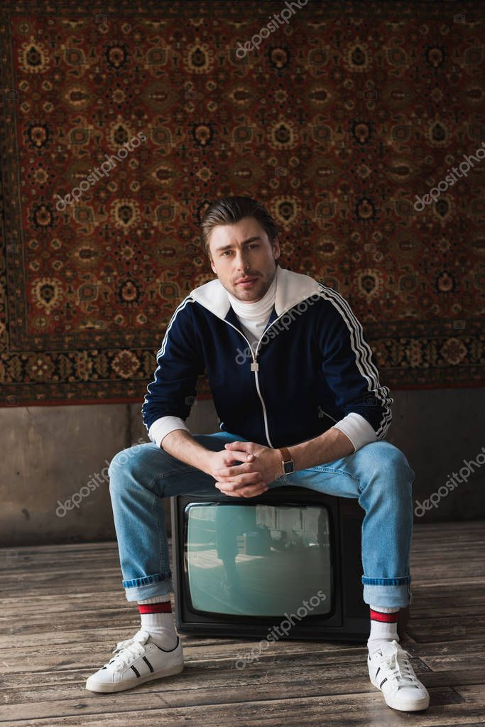 Handsome young man in vintage clothes sitting on retro tv set and looking at camera in front of rug hanging on wall