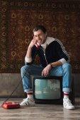 Fotografie usmíval se mladý muž v oblečení sedí na retro tv nastavit a mluví po telefonu před koberec visí na zdi