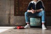 csinos, fiatal férfi ült a retro vintage ruhát tv vízpari piros vezetékes telefon előtt szőnyeg lógott a falon