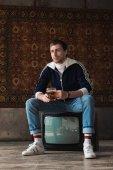 korsó sör ül a retro vintage ruha, elegáns fiatalember tv beállítása előtt szőnyeg lógott a falon