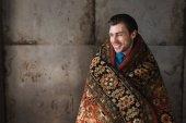 šťastný mladý muž něž v koberec před betonovou zeď