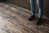 Fotografie oříznuté zastřelil člověka v stylové džíny a boty na dřevěnou podlahu