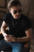 Photo attractive young man in black t-shirt and sunglasses sitting on chair