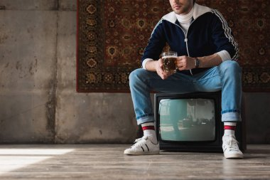 cropped shot of young man in vintage clothes with mug of beer sitting on retro tv set in front of rug hanging on wall