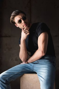 thoughtful young man in black t-shirt with sunglasses looking away
