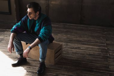 handsome young man in vintage windcheater sitting on wooden box in loft room