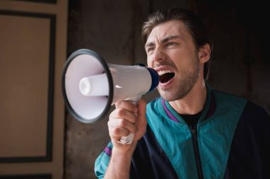mad young man in vintage windcheater shouting with loudspeaker