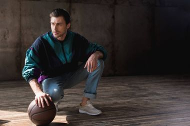 handsome young man in vintage windcheater with basketball ball sitting squats on wooden floor
