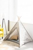 Photo close up view of childish teepee with pillows in room