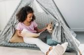 Kniha čtení malé africké americké dítě s pes chihuahua poblíž tím v teepee doma