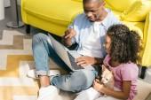 Fényképek afro-amerikai apa és kislányom kutya használ laptop otthon együtt