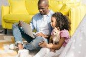 Fotografia afro-americano padre e piccola figlia con il cane mezzo computer portatile insieme a casa