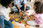 Fotografie částečný pohled africké americké rodiny hrát s barevnými bloky dohromady na podlahu doma