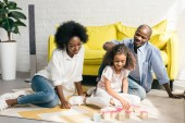Fotografie african american parents and daughter playing with wooden blocks together on floor at home
