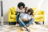 Photo smiling african american parents and little daughter reading book together at home
