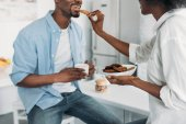 Fotografie částečný pohled afroamerické ženy krmení manžel s cookies v ráno v kuchyni doma