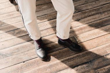 cropped shot of man in stylish shoes and pants standing on rustic wooden floor