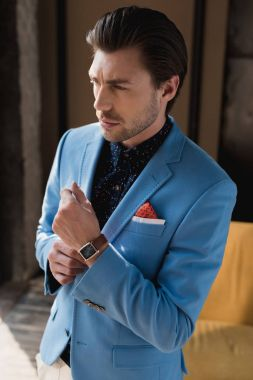 handsome young man in stylish blue jacket with wristwatch