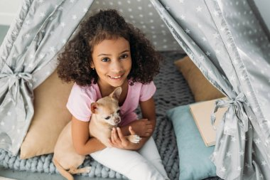 overhead view of little smiling african american kid with chihuahua dog in teepee at home