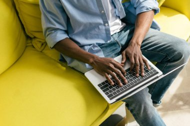partial view of african american man typing on laptop on sofa at home