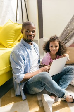 african american father with laptop and daughter with dog sitting on floor together at home