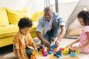 african american father and kids playing with colorful blocks on floor together at home