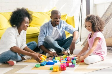 smiling african american family playing with colorful blocks together on floor at home