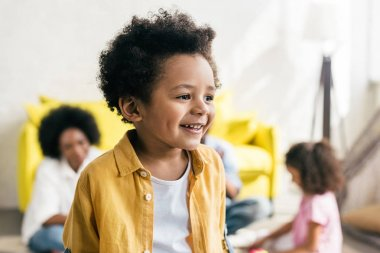 selective focus of smiling african american boy with family behind at home