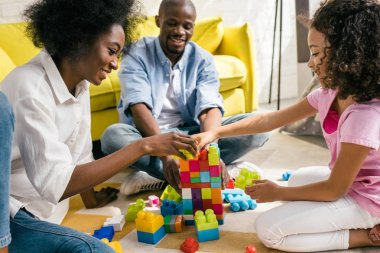 happy african american family playing with colorful blocks together on floor at home