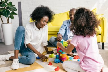 partial view of african american family playing with colorful blocks together on floor at home