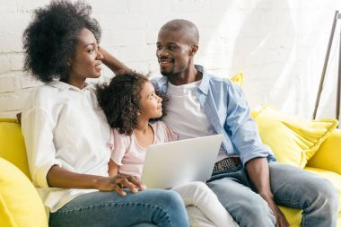 african american family with laptop resting on sofa together at home