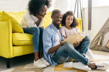 happy african american family reading book together at home