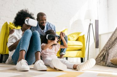 african american in virtual reality headset having fun together at home
