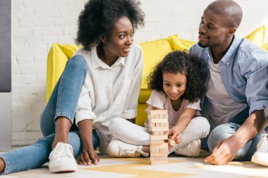 african american parents and daughter playing blocks tower game together at home